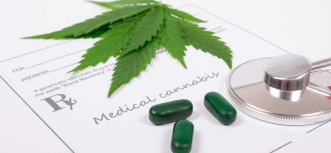 cannabis leaf near green pills and stethoscope