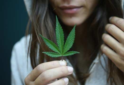 A woman holding a cannabis plant