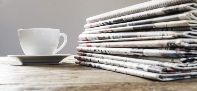 Neewspapers and coffee cup